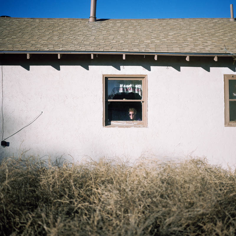 Woman with tumbleweeds in yard